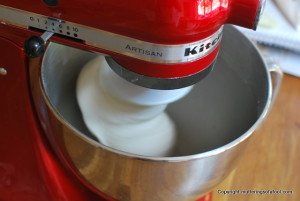 Red Kitchenaid mixing pizza dough
